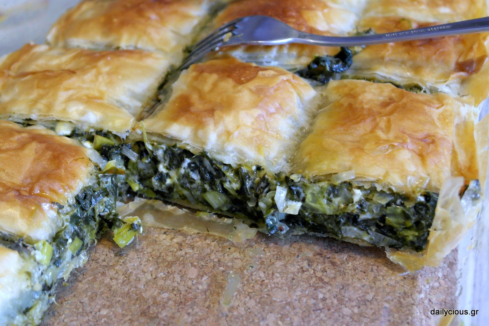 Preparing Greek spinach pie (traditional spanakopita)